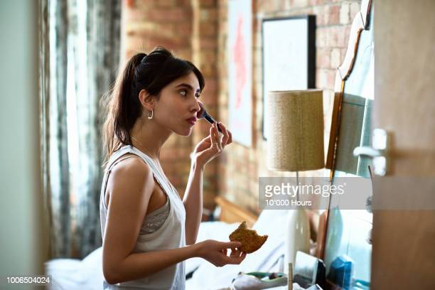 young woman applying blusher with make up and holding toast - preparation stock pictures, royalty-free photos & images