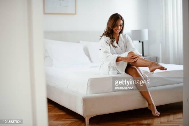 mujer joven aplicar crema de manos - celulitis fotografías e imágenes de stock