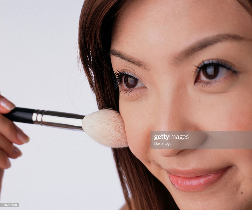 Young woman applying brusher : Stock Photo