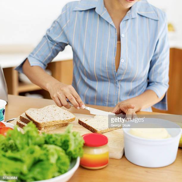 Young woman applying butter to a slice of brown bread