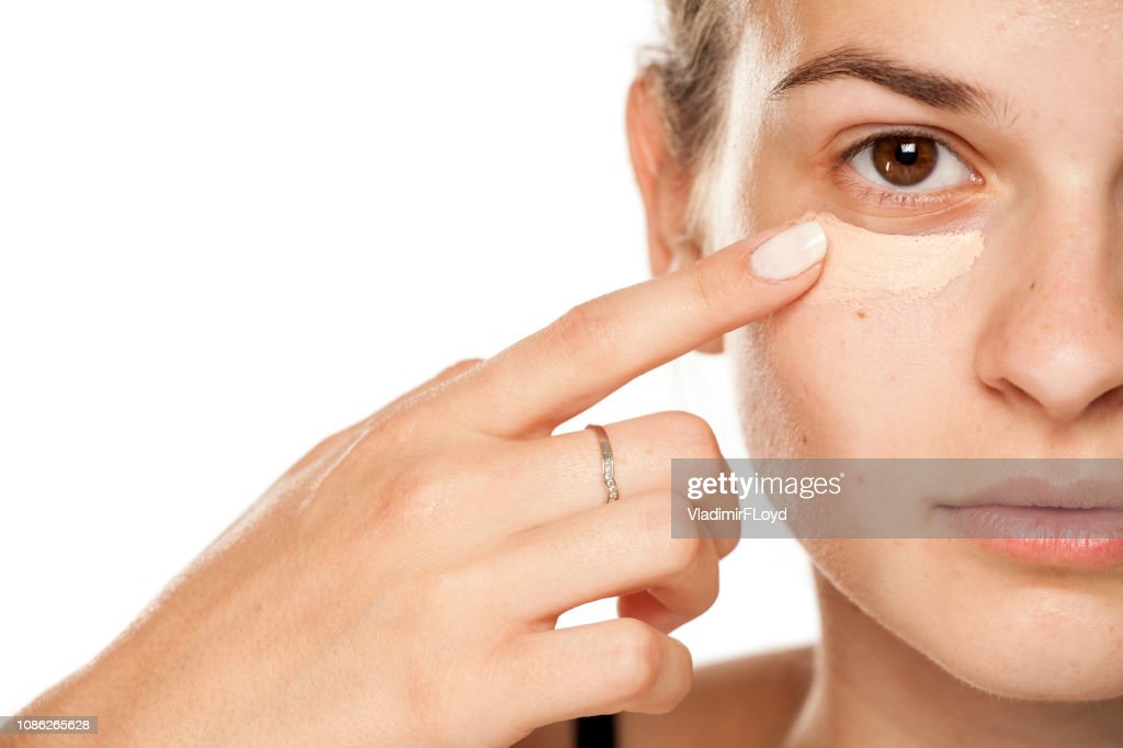 Young woman applying concealer under her eyes on white background : Stock Photo