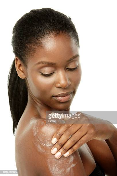 Young woman applying cream to her shoulder