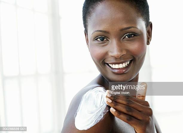 young woman applying cream to shoulder, smiling, portrait - chica adulta negra espalda desnuda fotografías e imágenes de stock