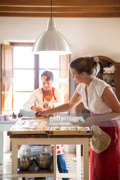 Young woman applying dried lavender to soap bars in handmade soap workshop