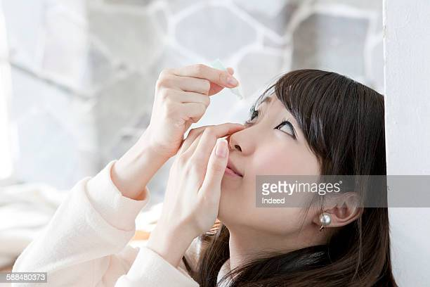 Young woman applying eye drops