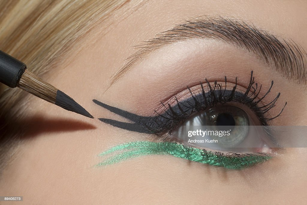 Young woman applying eye make up, close up. : Stock Photo
