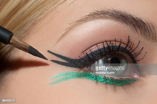 Young woman applying eye make up, close up.