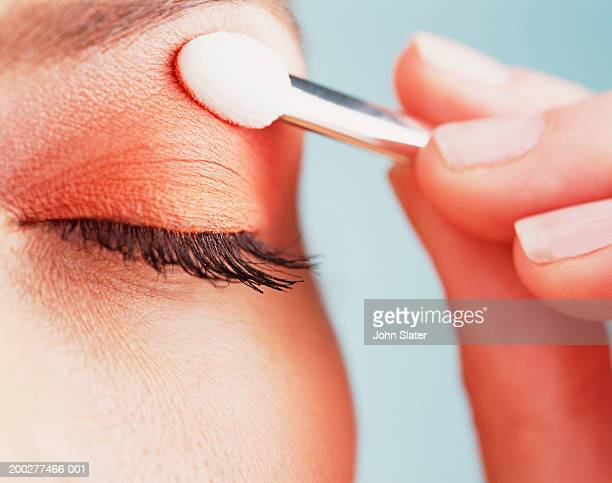 young woman applying eye shadow, close-up of eye - アイメイク ストックフォトと画像