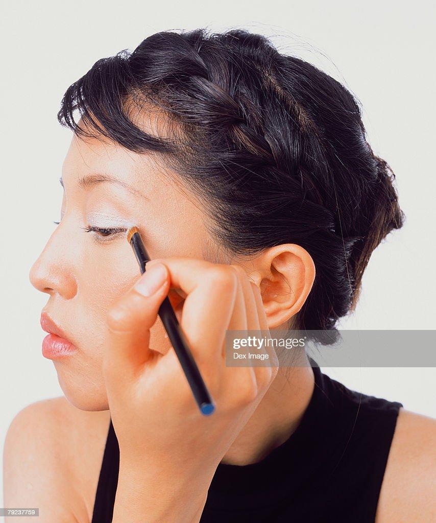 Young woman applying eye shadow : Stock Photo