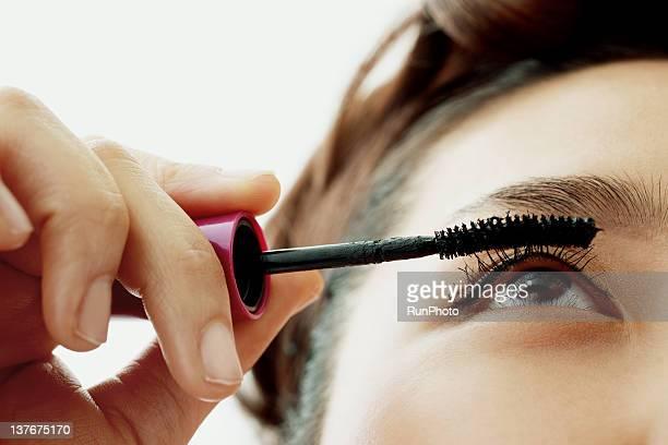 young woman applying eyelash makeup, close-up