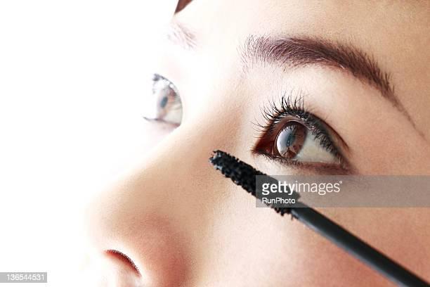 young woman applying eyelash make-up
