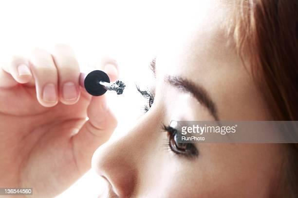 young woman applying eyelash,close-up