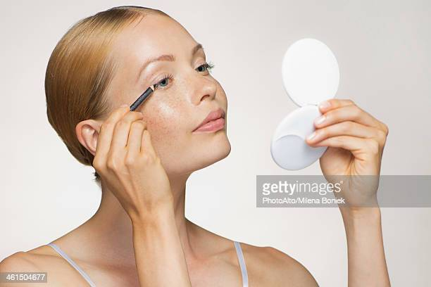 young woman applying eyeliner - powder compact stock pictures, royalty-free photos & images