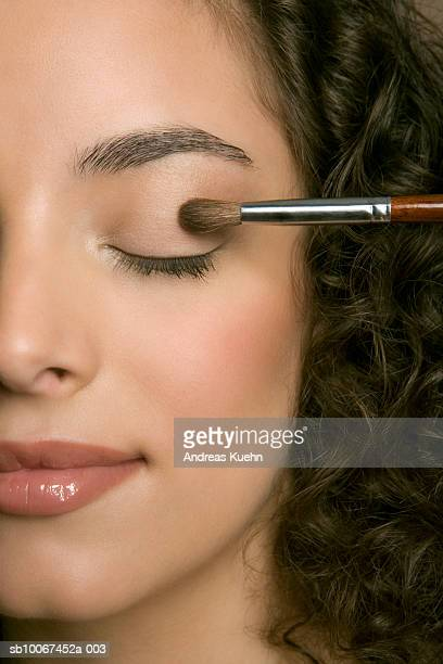 young woman applying eyeshadow, eyes closed, close-up - アイシャドウ ストックフォトと画像