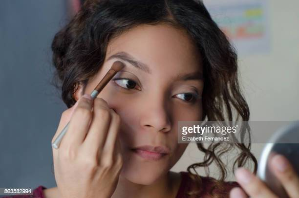 young woman applying eyeshadow to her brow bone - eyeshadow stock pictures, royalty-free photos & images