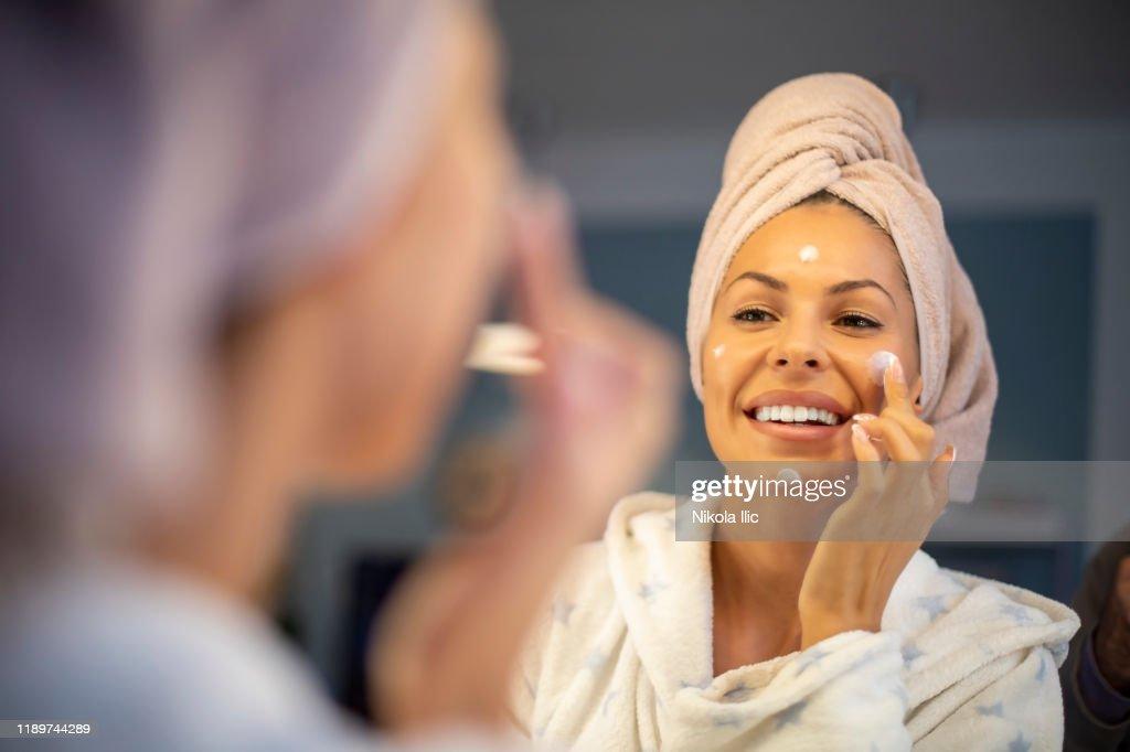 Jonge vrouw die gezichtscrème aanbrengt. : Stockfoto