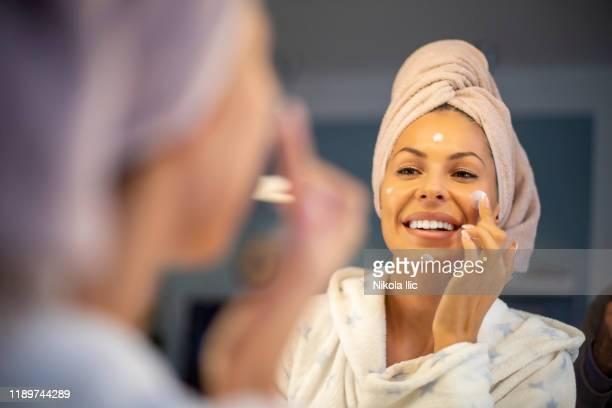 年輕女子應用面霜。 - 鏡 物品 個照片及圖片檔