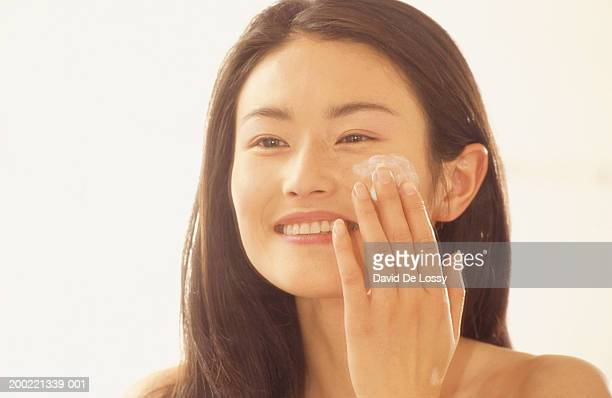 Young woman applying face cream,