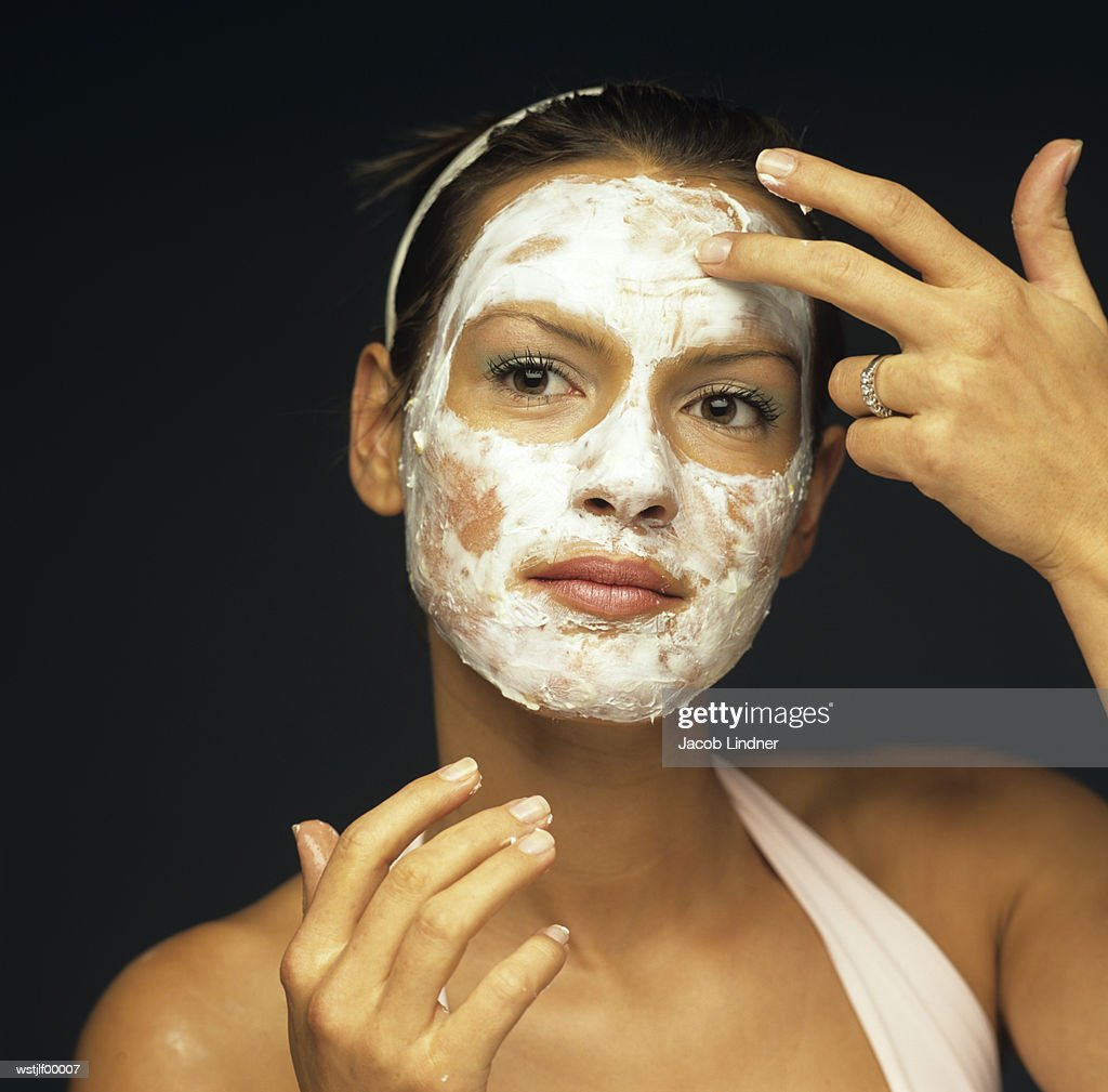 Young woman applying face pack, close up : Stock Photo