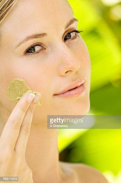 Young woman applying face scrub cream on her face, outdoors