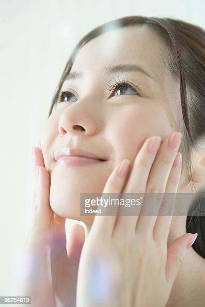Young woman applying facial cream, looking up