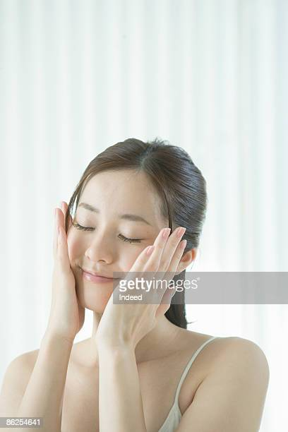 Young woman applying facial lotion, smiling