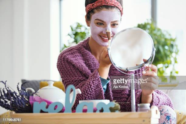 young woman applying facial mask. - skin feature stock pictures, royalty-free photos & images