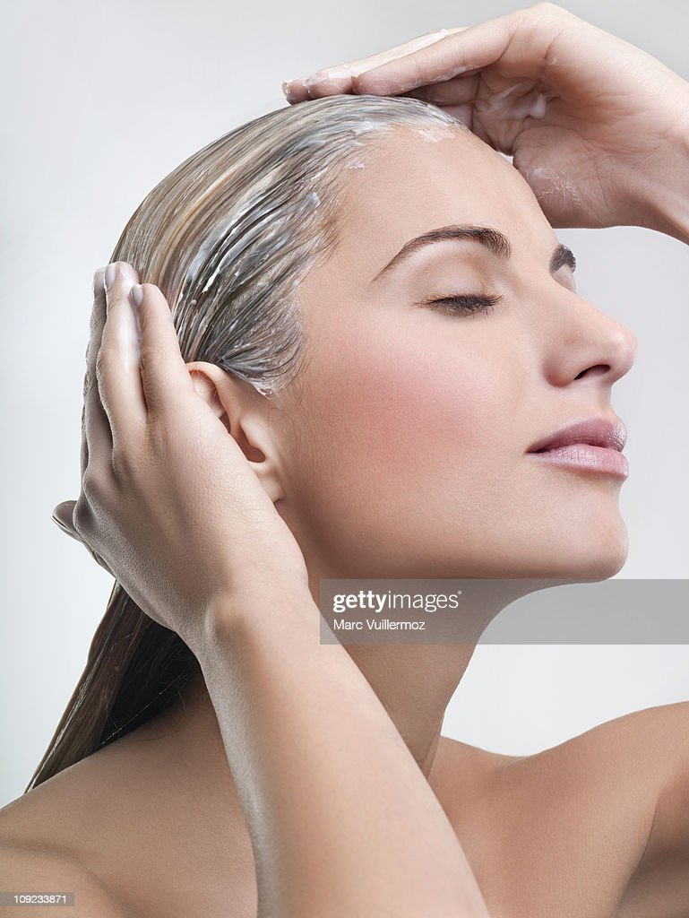 Young woman applying hair mask : ストックフォト