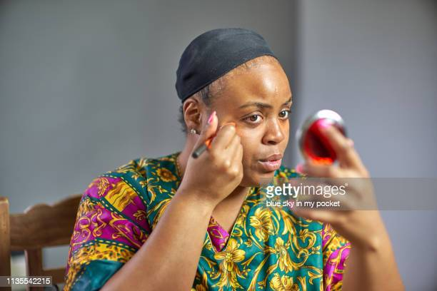 a young woman applying her own make-up. - concealer stock pictures, royalty-free photos & images