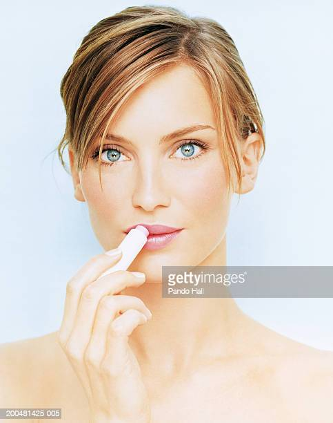 young woman applying lip balm, close-up, portrait - lip balm stock pictures, royalty-free photos & images