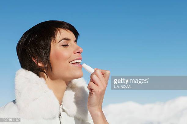 young woman applying lip balm - lip balm stock pictures, royalty-free photos & images