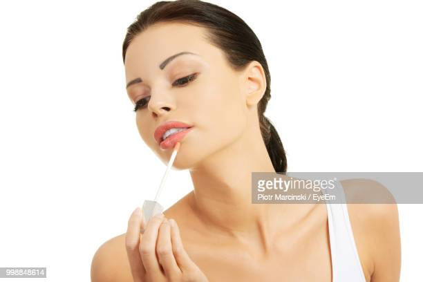 Young Woman Applying Lip Gloss Against White Background