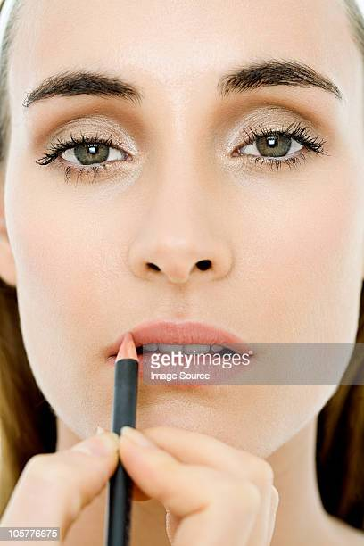 young woman applying lip liner - lip liner stock photos and pictures