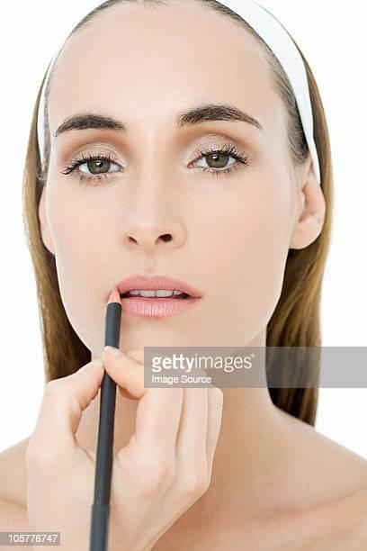 Junge Frau benutzt Lippenstift Futter