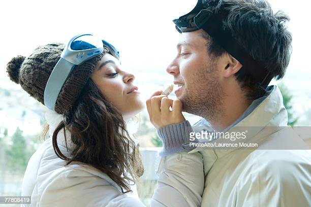 young woman applying lipbalm to boyfriend's lips, both dressed in winter clothing, side view - lip balm stock pictures, royalty-free photos & images