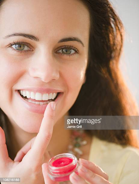 young woman applying lipgloss - lip gloss stock pictures, royalty-free photos & images