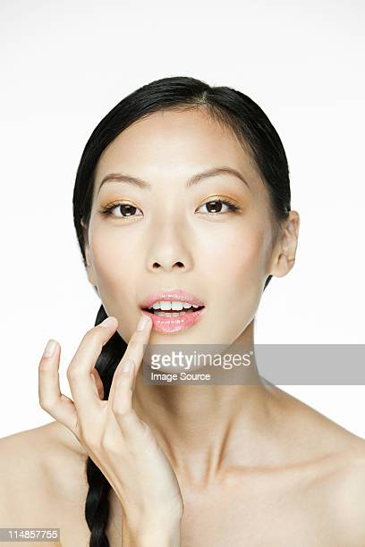 Young woman applying lipgloss