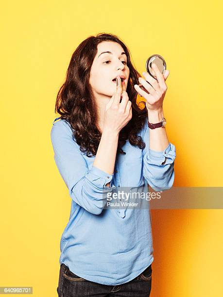 young woman applying lipstick against yellow background - powder compact stock pictures, royalty-free photos & images