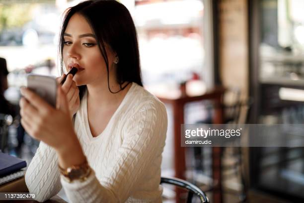 young woman applying lipstick at a cafe - matte lips stock pictures, royalty-free photos & images
