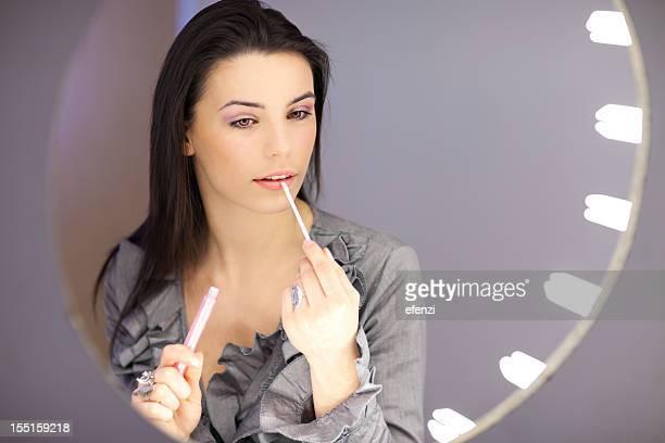 Jeune femme appliquant du rouge à lèvres sur un miroir de maquillage
