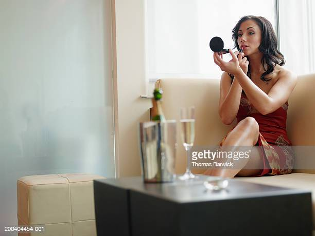 Young woman applying lipstick in compact mirror in nightclub
