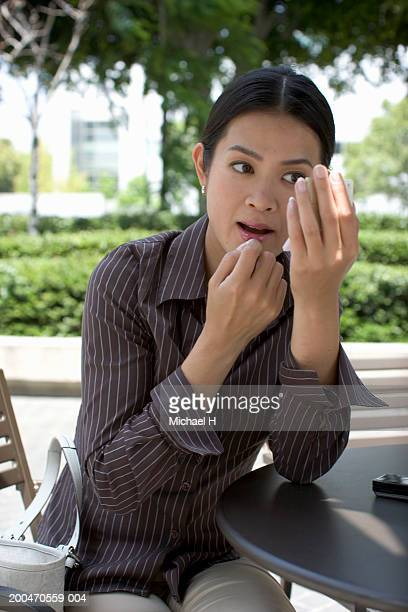Young woman applying lipstick in compact mirror