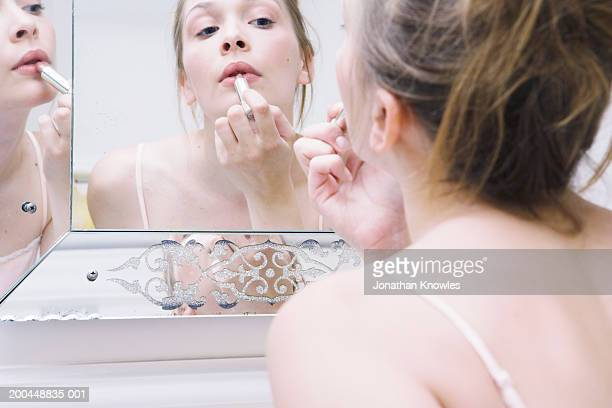 Young woman applying lipstick in mirror (focus on reflection)
