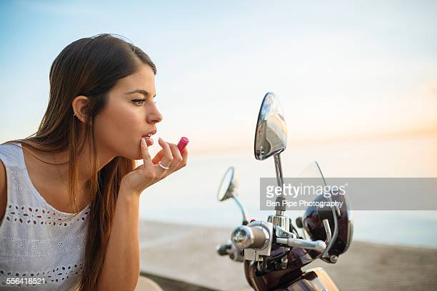 Young woman applying lipstick in motorcycle mirror, Manila, Philippines