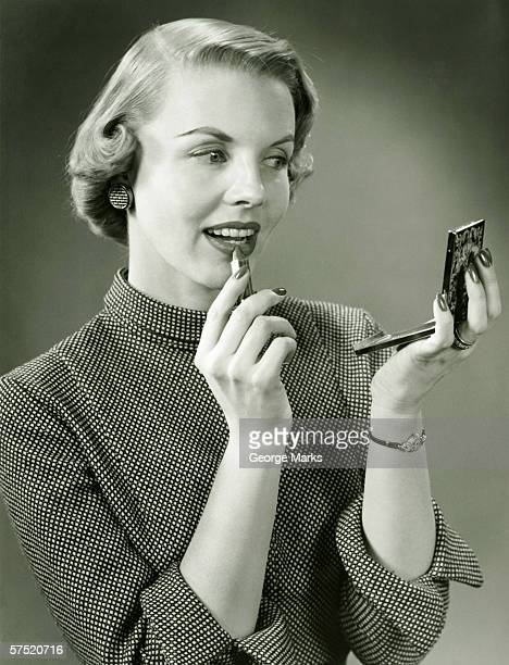 Young woman applying lipstick, looking at powder compact mirror, (B&W), close-up