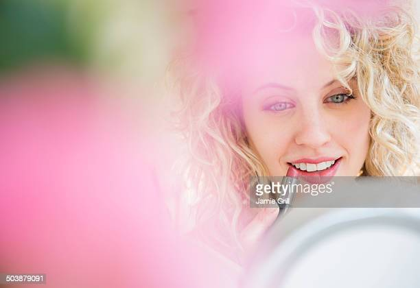 young woman applying lipstick - focus on background stock pictures, royalty-free photos & images