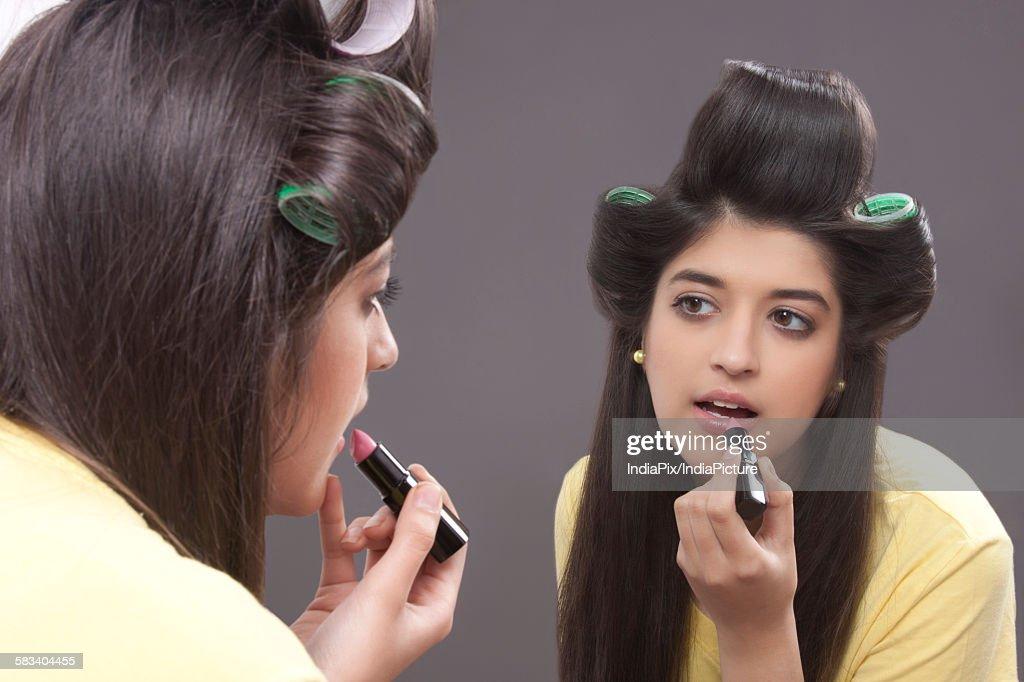 Young woman applying lipstick : Stock Photo