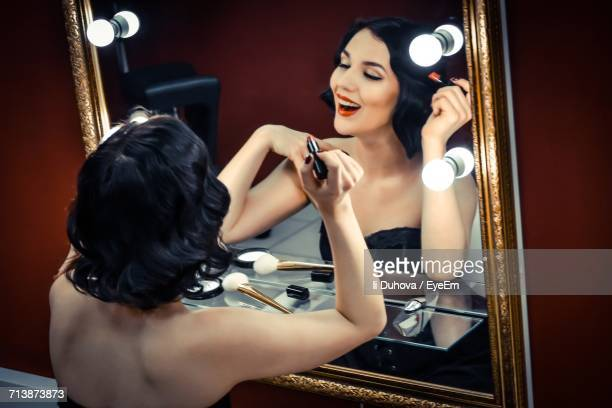young woman applying lipstick - actress stock pictures, royalty-free photos & images