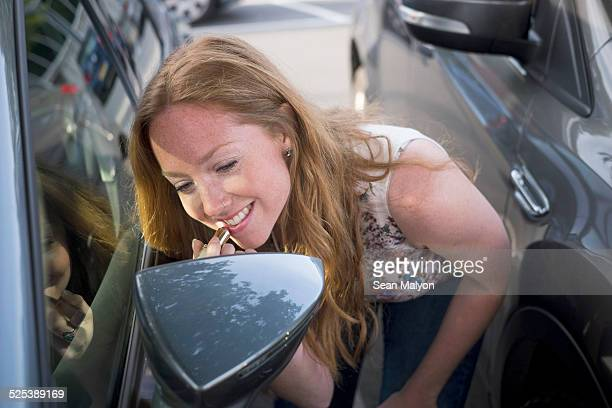 Young woman applying lipstick whilst looking in car wind mirror