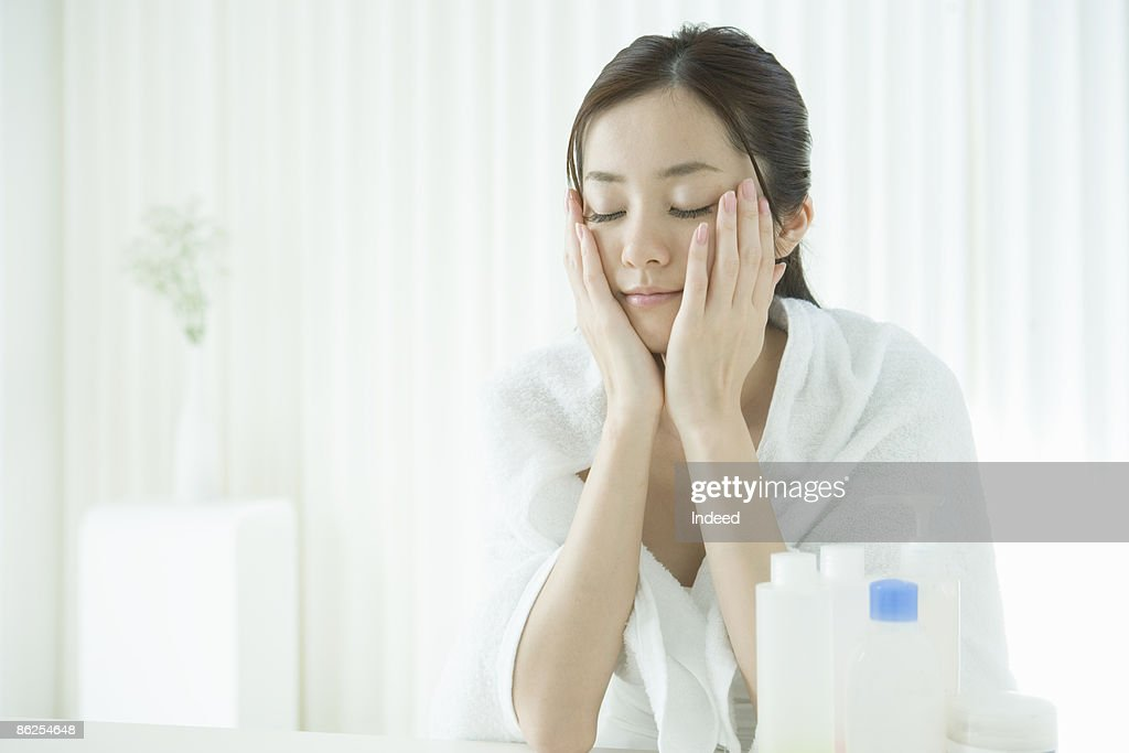 Young woman applying lotion, eyes closed : ストックフォト